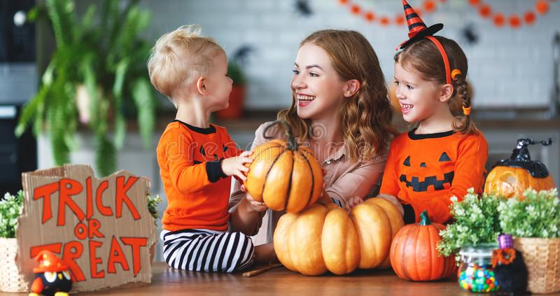 Happy Halloween! family mother and children getting ready for ho. Liday cutting a pumpkin royalty free stock images