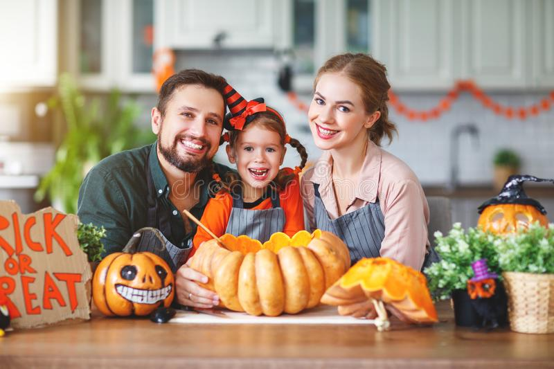 Happy Halloween! family mother father and child daughter cut pumpkin for holiday home. Happy Halloween! family mother father and child daughter cut a pumpkin for stock photo