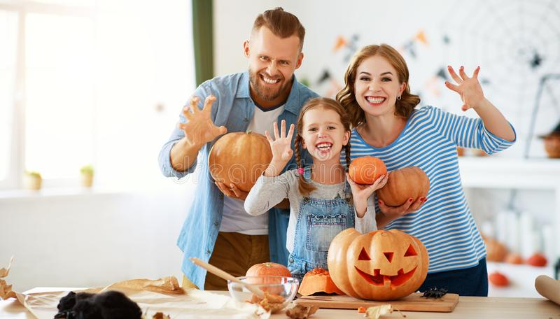 Happy Halloween! family mother father and child daughter cut pumpkin for holiday at home royalty free stock images