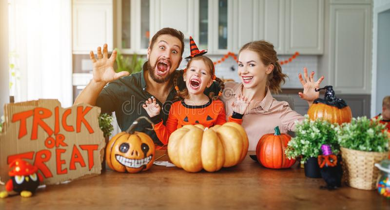 Happy Halloween! family mother father and child daughter cut pu. Happy Halloween! family mother father and child daughter cut a pumpkin for holiday home stock photography