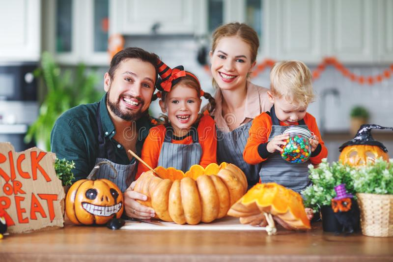 Happy Halloween! family mother father and children cut pumpkin f. Happy Halloween! family mother father and children cut a pumpkin for holiday home royalty free stock image
