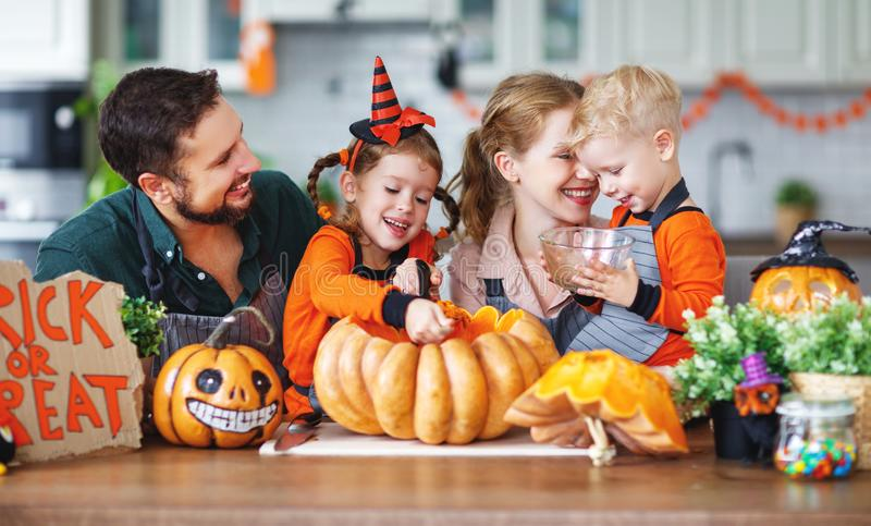 Happy Halloween! family mother father and children cut pumpkin f. Happy Halloween! family mother father and children cut a pumpkin for holiday home stock photos