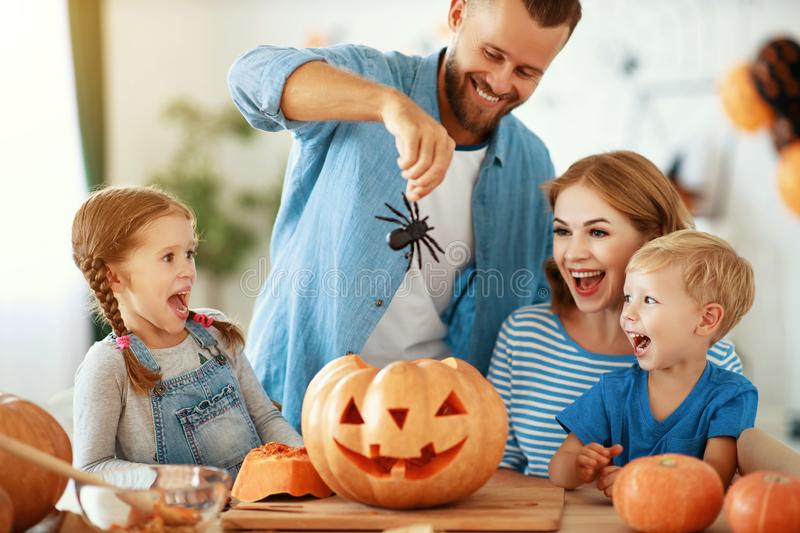 Happy Halloween! family mother father and children cut pumpkin for holiday at home stock images
