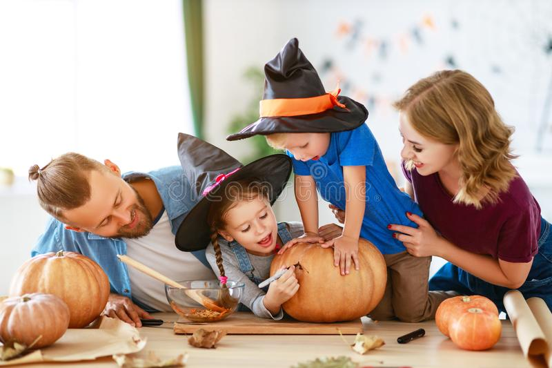 Happy Halloween! family mother father and children cut pumpkin for holiday at home royalty free stock photos