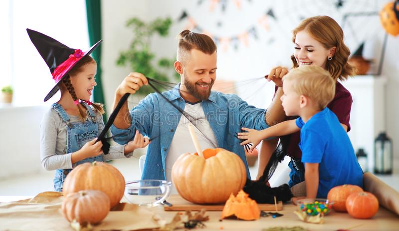 Happy Halloween! family mother father and children cut pumpkin for holiday at home stock image