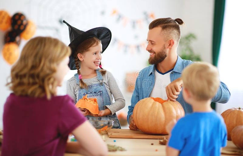 Happy Halloween! family mother father and children cut pumpkin for holiday at home royalty free stock image