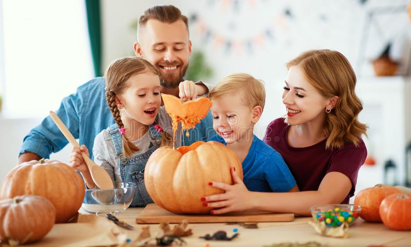 Happy Halloween! family mother father and children cut pumpkin for holiday at home. Happy Halloween! family mother father and children cut a pumpkin for holiday royalty free stock images