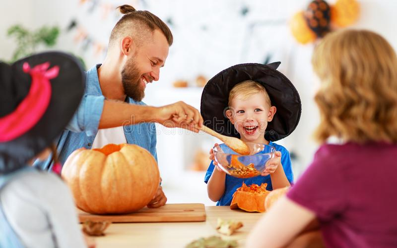 Happy Halloween! family mother father and children cut pumpkin for holiday at home royalty free stock images
