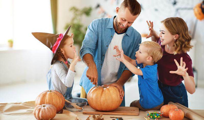 Happy Halloween! family mother father and children cut pumpkin for holiday at home stock photos