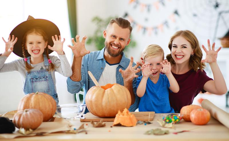Happy Halloween! family mother father and children cut pumpkin for holiday at home royalty free stock photography