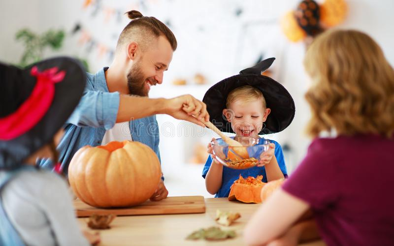 Happy Halloween! family mother father and children cut pumpkin for holiday at home. Happy Halloween! family mother father and children cut a pumpkin for holiday stock images