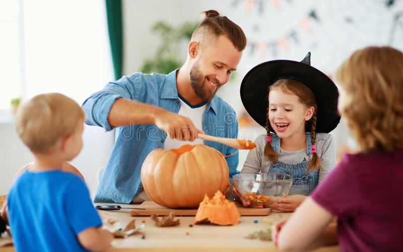 Happy Halloween! family mother father and children cut pumpkin for holiday at home. Happy Halloween! family mother father and children cut a pumpkin for holiday royalty free stock photography