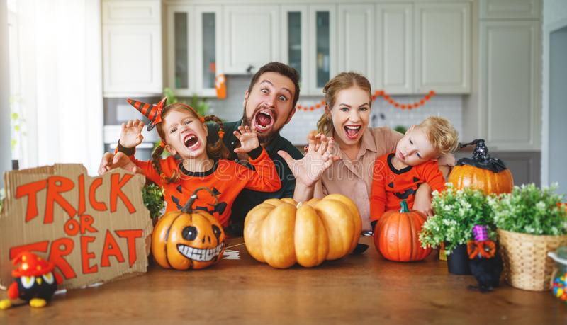 Happy Halloween! family mother father and children cut pumpkin f. Happy Halloween! family mother father and children cut a pumpkin for holiday home royalty free stock photos