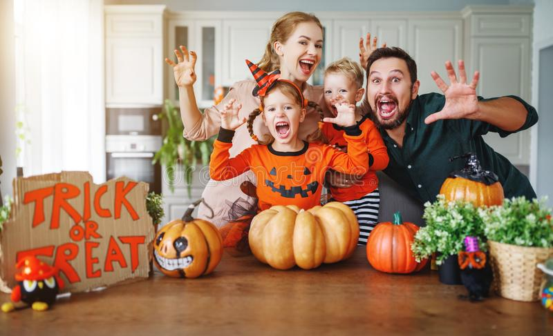 Happy Halloween! family mother father and children cut pumpkin f. Happy Halloween! family mother father and children cut a pumpkin for holiday home royalty free stock photography