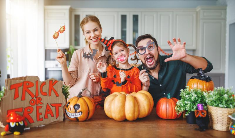 Happy Halloween! family mother father and children cut pumpkin f. Happy Halloween! family mother father and children cut a pumpkin for holiday home royalty free stock images