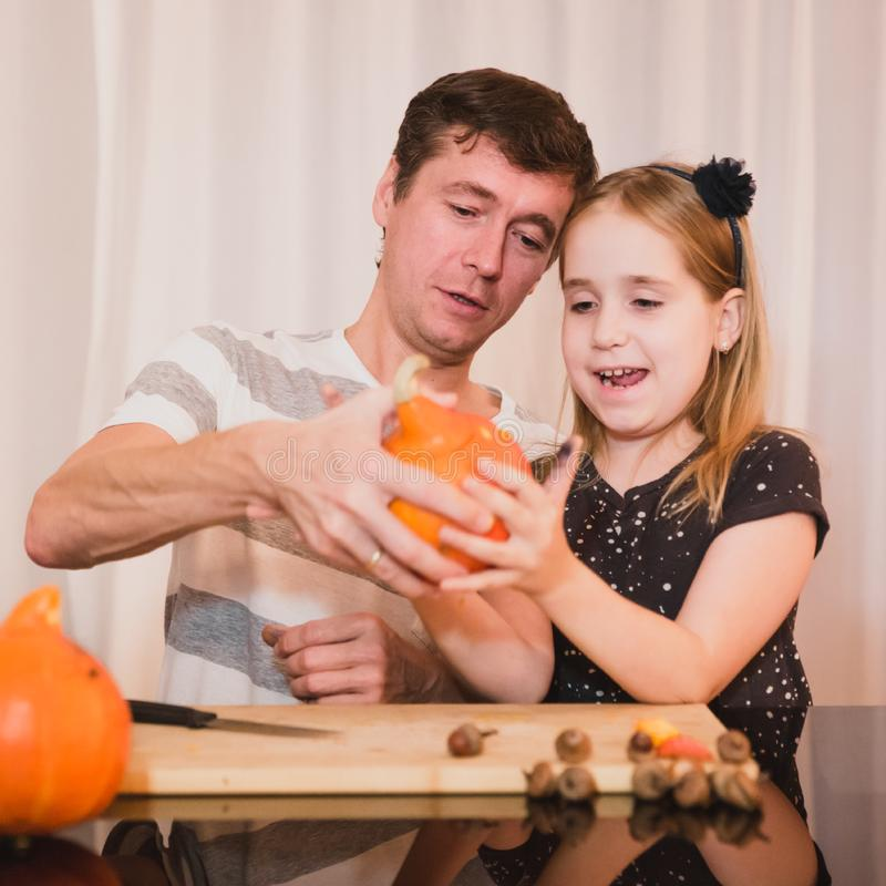 Happy halloween. Father and daughter carving pumpkin for Halloween at home royalty free stock photos