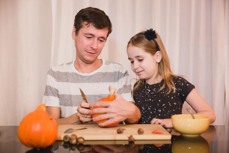 Happy halloween. Father and daughter carving pumpkin for Halloween at home. Happy family stock images