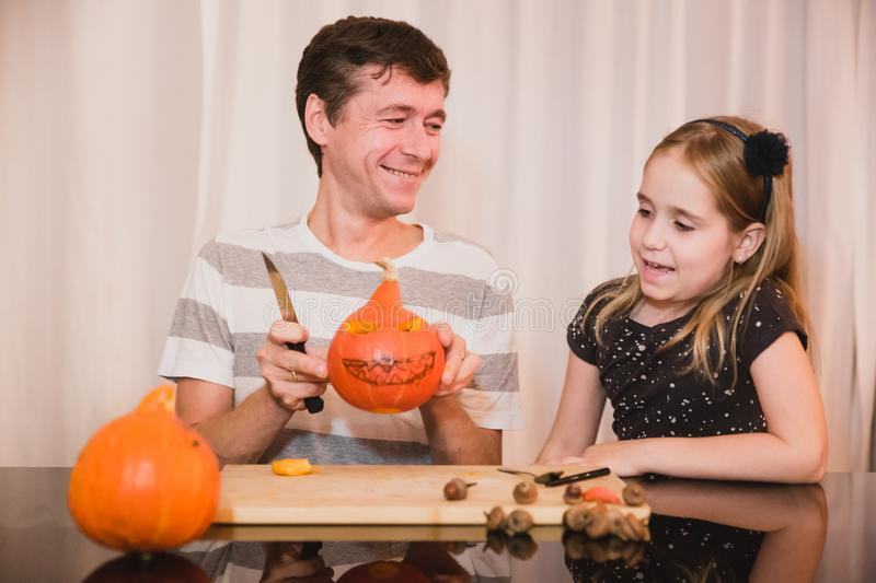 Happy halloween. Father and daughter carving pumpkin for Halloween at home. Happy family stock photography
