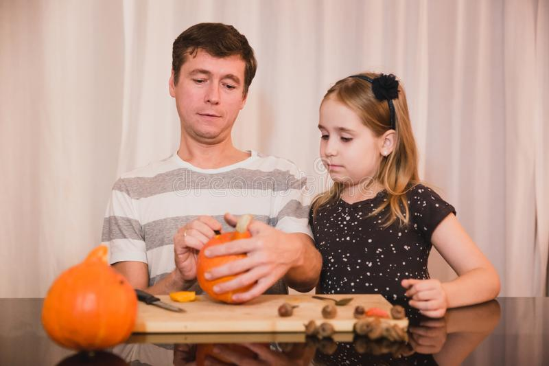Happy halloween. Father and daughter carving pumpkin for Halloween at home. Happy family royalty free stock photo