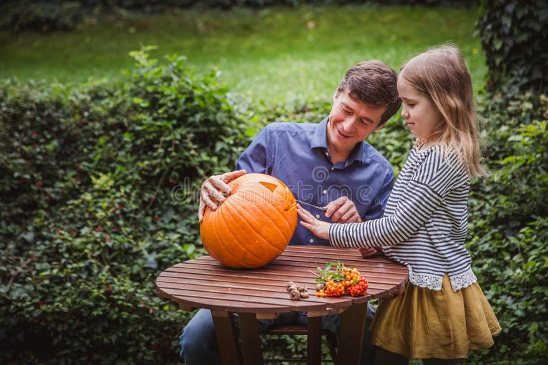 Happy halloween. Father and daughter carving pumpkin for Halloween outside. Autumn stock photos