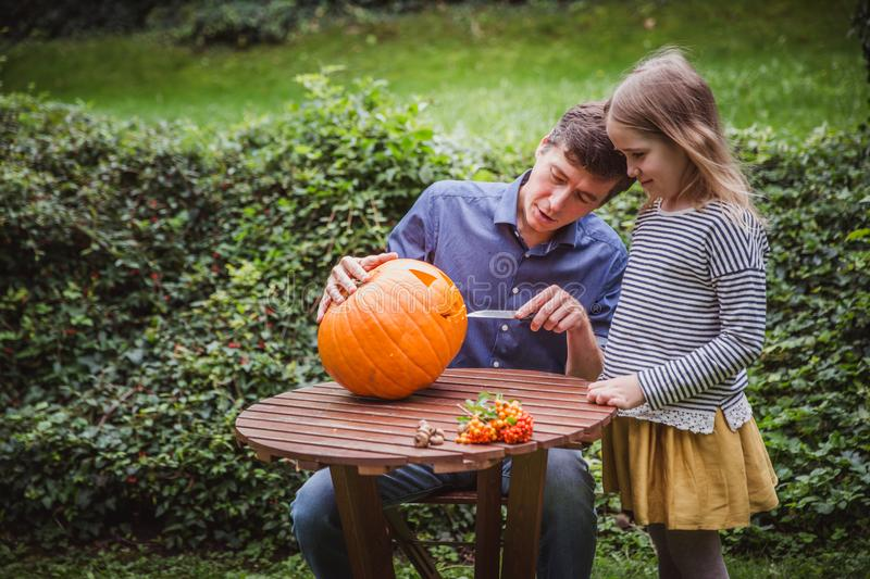 Happy halloween. Father and daughter carving pumpkin for Halloween outside. Autumn royalty free stock images