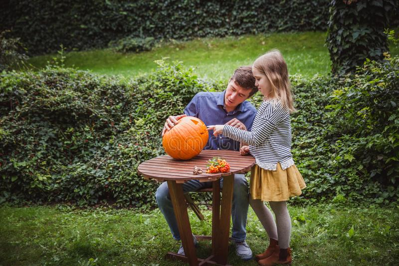 Happy halloween. Father and daughter carving pumpkin for Halloween outside. Autumn royalty free stock photography
