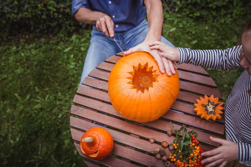 Happy halloween. Father and daughter carving pumpkin for Halloween outside high angle view, hands. Happy family royalty free stock images