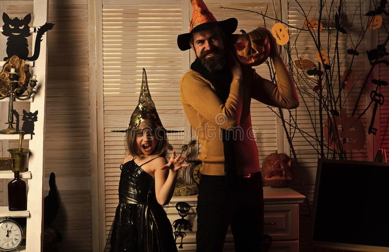Happy Halloween. Father and daughter with Halloween decor. Halloween party concept. Girl and bearded men with wild faces on red spooky carnival room background stock photo