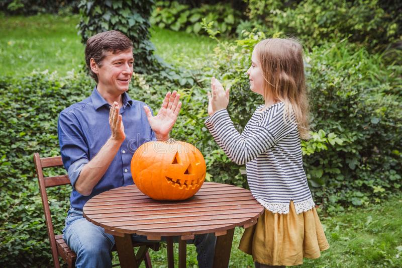 Happy halloween. Father and daughter playing with a pumpkin outside. A happy family royalty free stock images