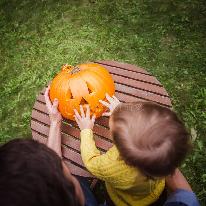 Happy halloween. Father and small daughters look at the face cut in the pumpkin high angle view. Outside. Autumn royalty free stock photos
