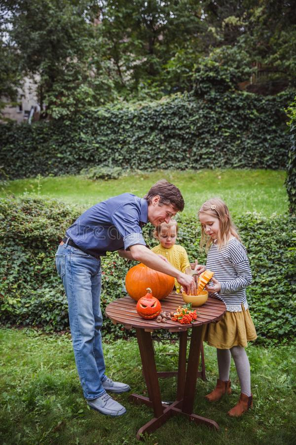 Happy halloween. Father and two daughter carving pumpkin for Halloween outside and pulls seeds and fibrous material from royalty free stock image