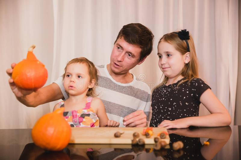 Happy halloween. Father and two daughters carving pumpkin for Halloween at home. Happy family stock image