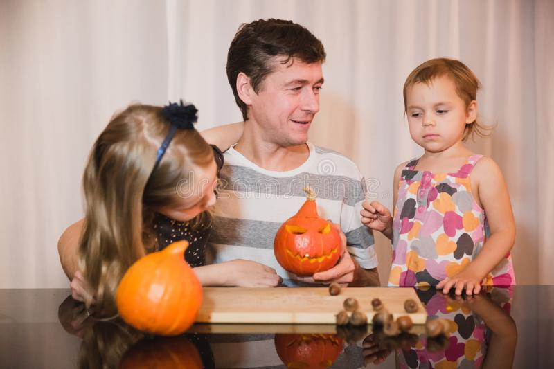 Happy halloween. Father and two daughters carving pumpkin for Halloween at home. Happy family stock photos