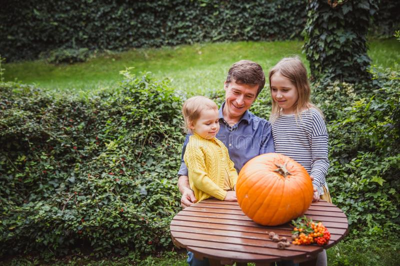 Happy halloween. Father and two daughters look at the face cut in the pumpkin for Halloween outside. royalty free stock photo