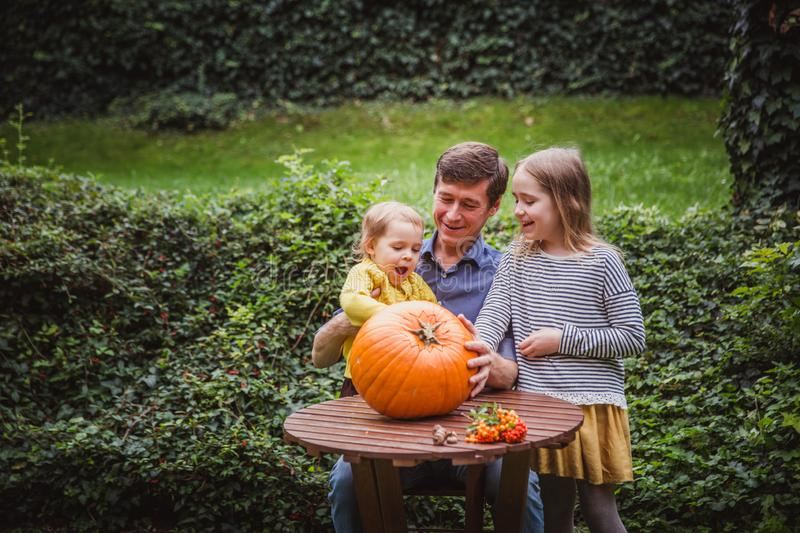 Happy halloween. Father and two daughters look at the face cut in the pumpkin for Halloween outside. stock photography