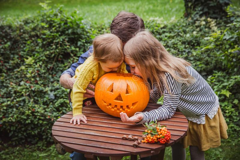Happy halloween. Father and two daughters look inside the carved pumpkin for Halloween outside. stock photos