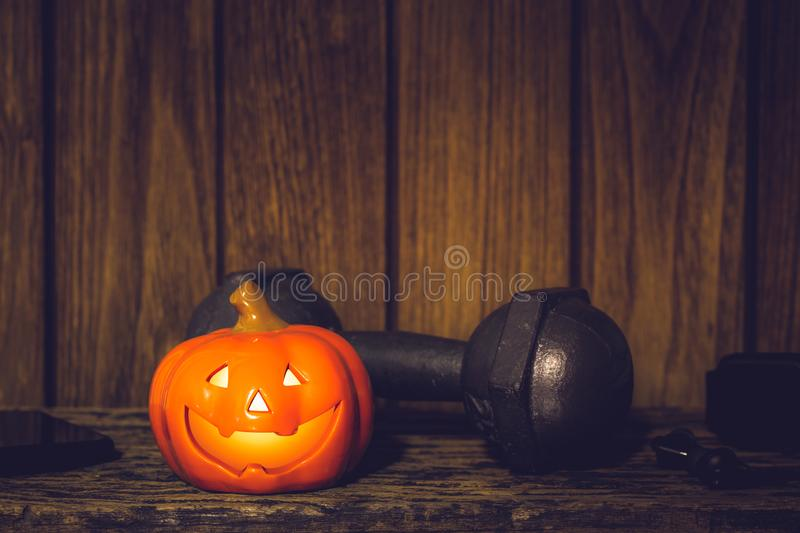Happy Halloween festival background concept. Close up of Halloween head Pumpkins doll and the black iron dumbbell and equipments. Fitness, healthy active royalty free stock photos