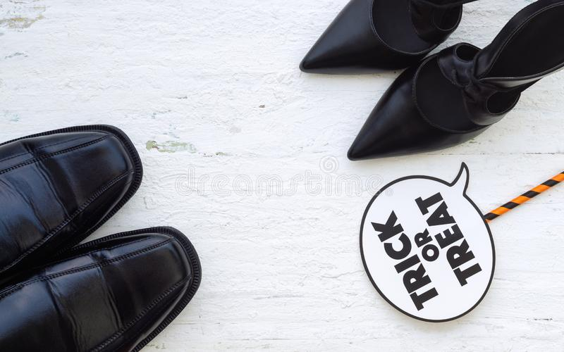 Happy Halloween Festival with female beauty high heels and male. Black leather shoes with trick or treat sign, Halloween fashion shopping and funny concept stock photography