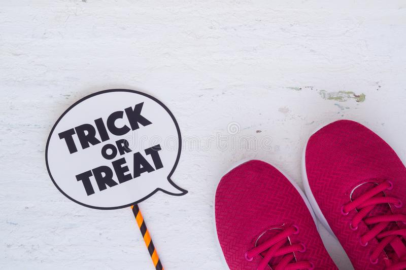 Happy Halloween Festival with red sport shoes and trick or treat. Sign on white wood background stock photo