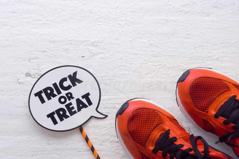 Happy Halloween Festival with sport shoes and trick or treat sign on white wood background stock photo