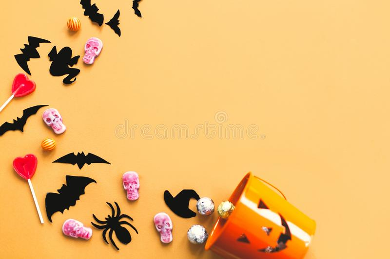 Happy Halloween flat lay, copy space. Halloween candy, skulls, black bats and ghost paper decorations scattered from evil bucket. On yellow background.Trick or royalty free stock photo