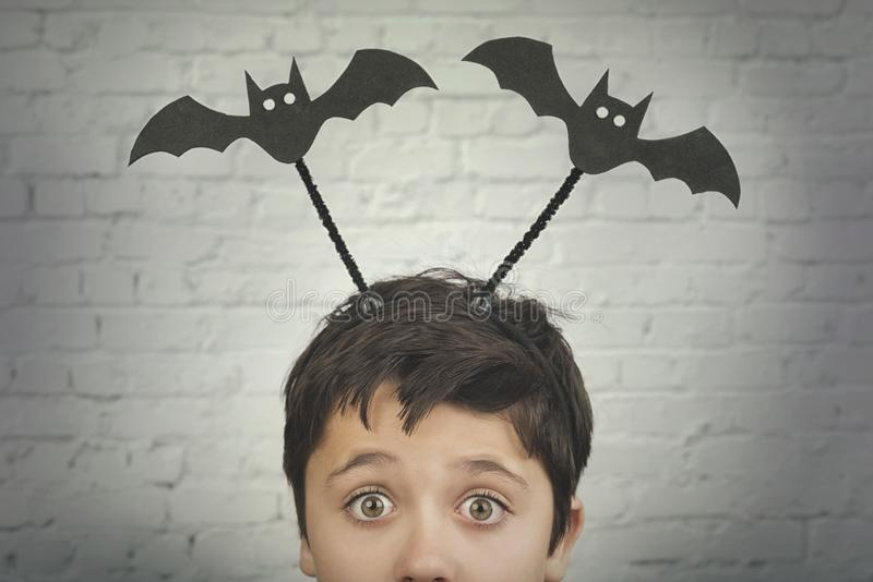 Happy Halloween.funny child with halloween vampires over on his head. Against brick .background stock photo