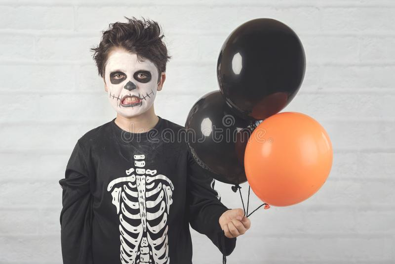 Happy Halloween. funny child in a skeleton costume with colorful balloons. Against brick .background stock photography