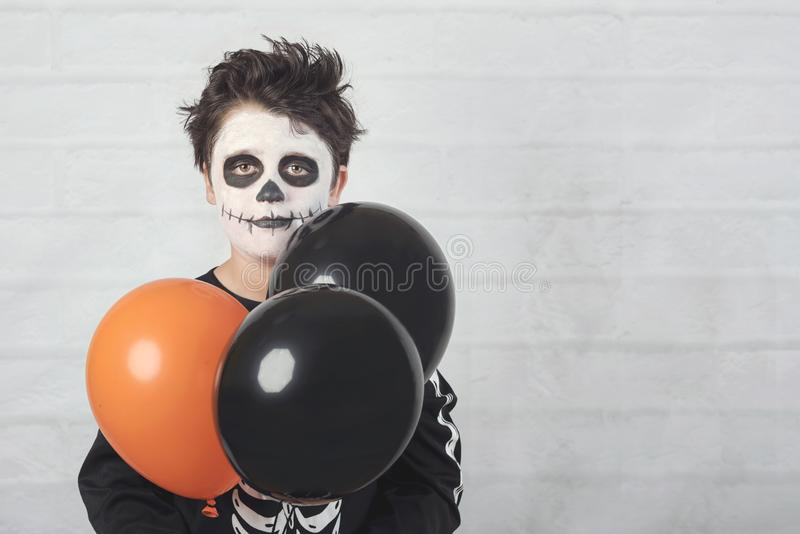Happy Halloween. funny child in a skeleton costume with colorful balloons. Against brick background royalty free stock image