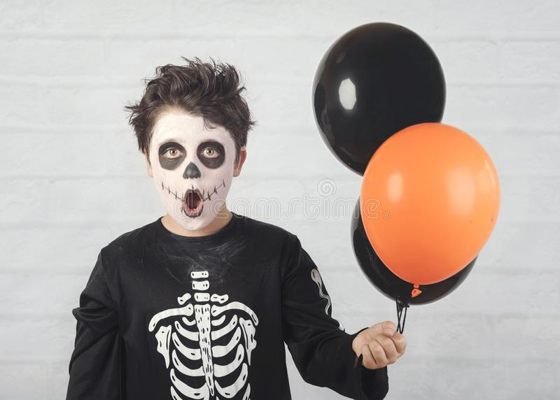 Happy Halloween. funny child in a skeleton costume with colorful balloons. Against brick background stock photography