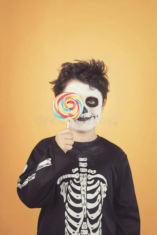 Happy Halloween.funny child in a skeleton costume covering eye with lollipop. Against .orange background royalty free stock image
