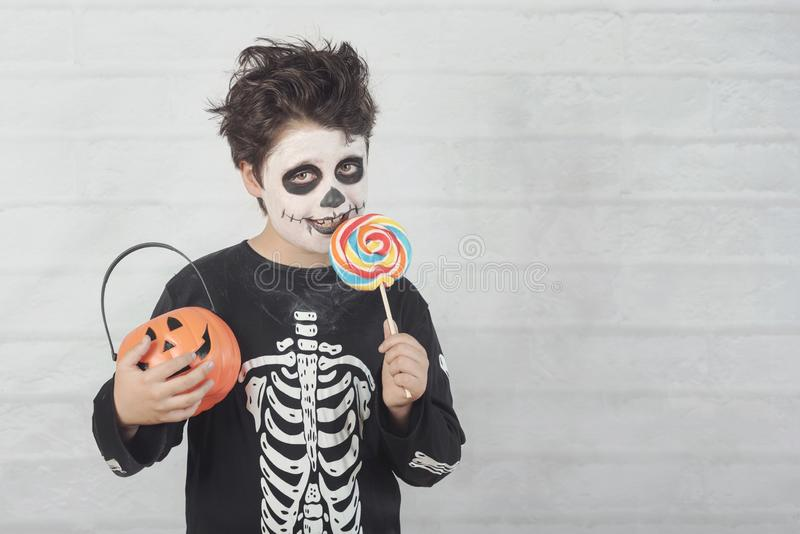 Happy Halloween.funny child in a skeleton costume eating lollipop in halloween. Against .brick background stock image