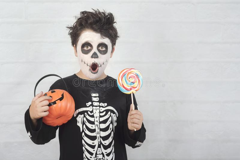 Happy Halloween.funny child in a skeleton costume eating lollipop in halloween. Against brick background stock photography