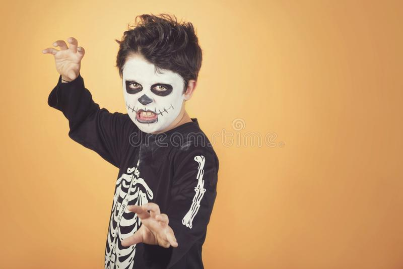 Happy Halloween. funny child in a skeleton costume of halloween. Against orange background stock image