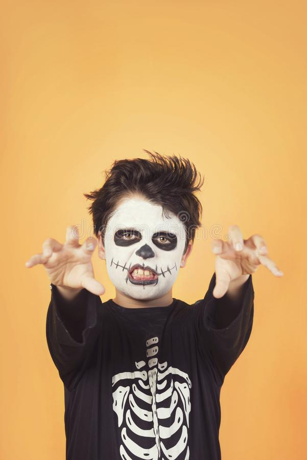 Happy Halloween. funny child in a skeleton costume of halloween. Against orange background stock photos